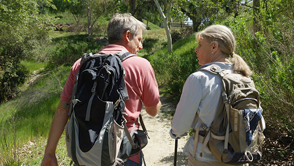Man and woman talking and walking down a trail